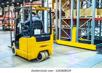 Forklift yellow. Warehouse automation. Boxes are on the shelves of the warehouse. Warehousing. Logistics in stock. Forklift rides through the warehouse.
