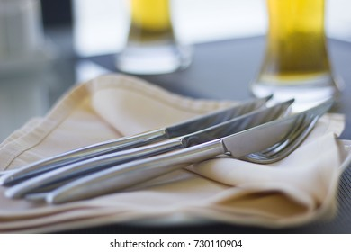 forks and knives lying on napkins in a cafe