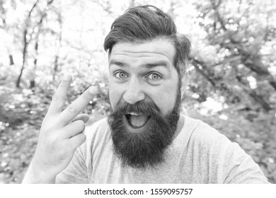 The forks. Man gesturing V sign as insult. Brutal man giving offensive gesture. Vulgar man with long mustache and beard hair outdoor. Bearded man in casual style on natural landscape.
