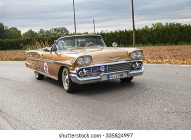 "FORLI', ITALY - SEPTEMBER 20: driver and co-driver on American vintage car Chevrolet Impala Convertible (1958) in classic car rally ""Gran Premio Nuvolari"" on September 20, 2015 in Forli, Italy"