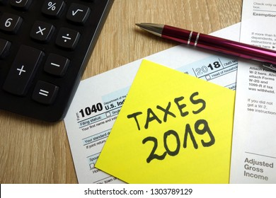 Form 1040, calculator and pen on desk, tax season 2019