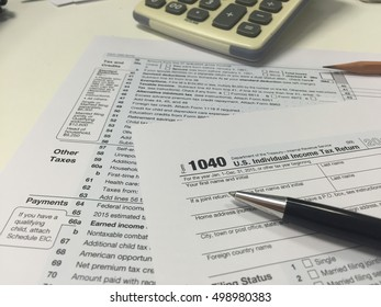 Form 1040, U.S. Individual income tax return place on table with calculator and pen