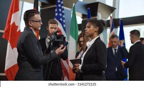 Formal African-American woman talking to journalist for camera and giving interview on international summit