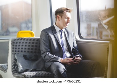 Formal business man sitting on the train with his bag. He is looking out the window and has a smart phone in his hands.