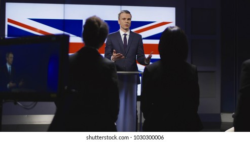 Formal businessman in suit standing on stage against screen with Great Britain flag and giving speech for auditorium in studio. Slow motion.