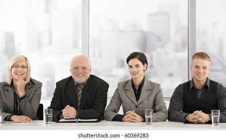 Formal businessteam portrait of different generations sitting at meeting table, smiling at camera.?