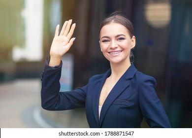 Die formell gekleidete glückliche Geschäftsfrau winkt ihre Hand im Freien und lächelt. Junge Büromädchen in Anzug, Jacke heißt willkommen. Attraktive Dame, die ihr Kollegium grüßt und Hallo sagt