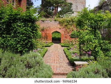 A Formal english Walled garden with path leading to an Arch through a brick wall