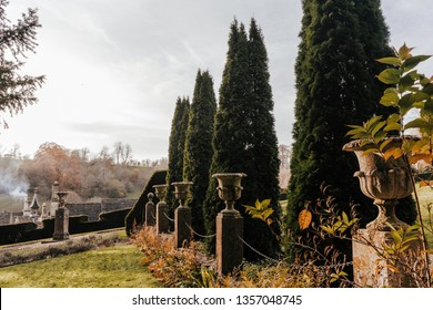 Formal garden design with line of stone urns and large conifers thuja, roof of country house at background with smoke comming out of chimney. Autumn. Castle Combe, England.
