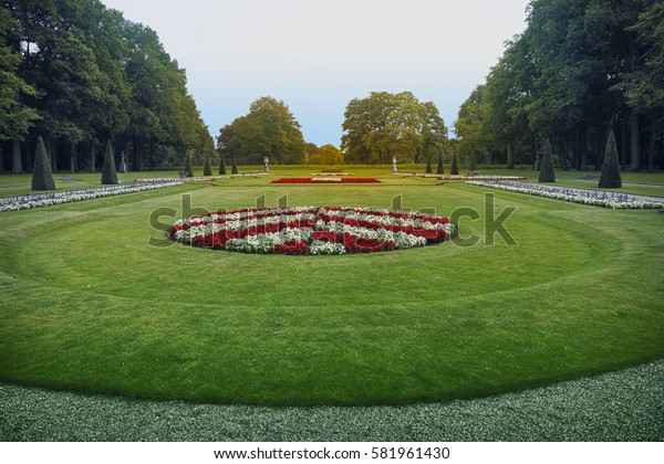 Formal garden with round flower bed surrounded by pyramidal bushes and big green trees.
