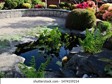 Formal garden with topiary shapes and forms water feature waterfall pond paver deck low retaining block wall background