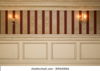 Formal interior wall with wallpaper, sconces and paneling