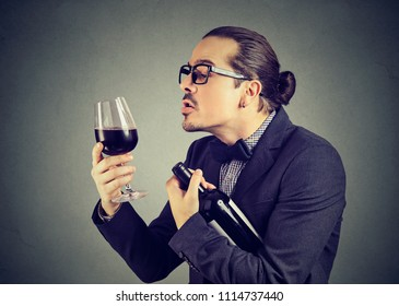 Formal ironic man holding bottle and glass of red wine looking with love to alcohol on gray background