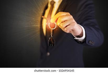 Formal man hand over shiny keys with dark background