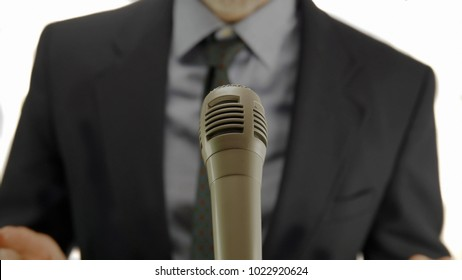 formal mature man speaking at the microphone