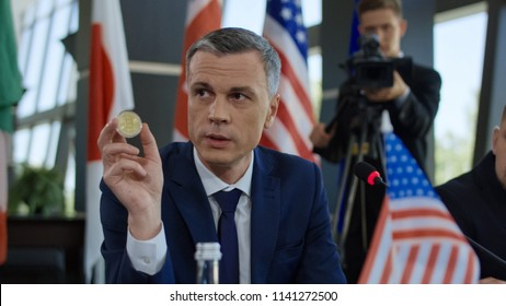Formal politician of American government making speech about bitcoin cryptocurrency showing golden coin at table on summit