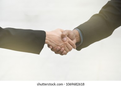 formal two businessman and businesswomen stakeholder wear suit have greeting by welcome warm handshake to congratulation together in sign contact business term deal also OK good promise to partner