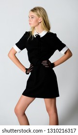 Formal uniform elite school college or housemaid. Vintage model. Elegance in simplicity. Fashionable uniform. Vintage and retro style. Vintage fashion concept. Girl blonde wear elegant black dress.