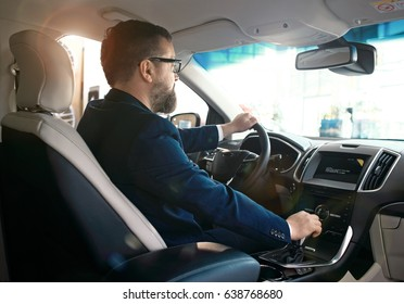 Formal wearing young man behind the wheel