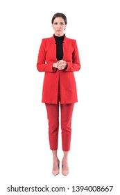 Formal young business woman in red suit with clasped hands looking at camera. Full body isolated on white background.