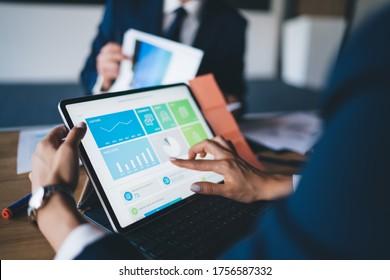 Formell gekleidete gesichtslose Frau, die Tablet-Computer-Entdeckungkarten verwendet, während sie während eines Geschäftstreffens mit Kollegen am Tisch sitzt