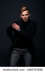 Formally dressed man with sharp jawline in his 20's posing in a studio in front of a black background.