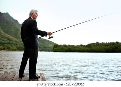 Formally dressed mature businessman fishing on the lake.