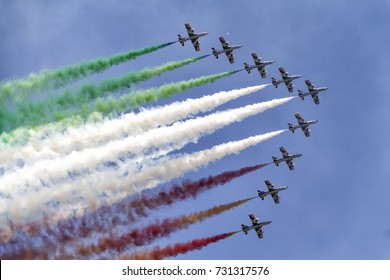 Formation of nine airplanes in the sky at an air show with colorful smoke