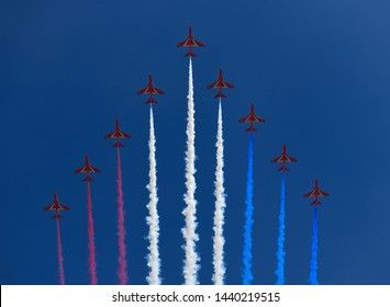 Formation of RAF Red Arrows with coloured trails on blue sky for flypast at Trooping the Colour for Queen Elizabeth's 93rd birthday London, England - June 8, 2019