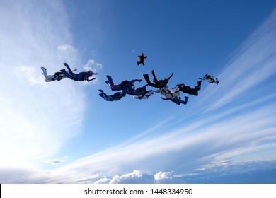 A formation of skydivers is in the sky.