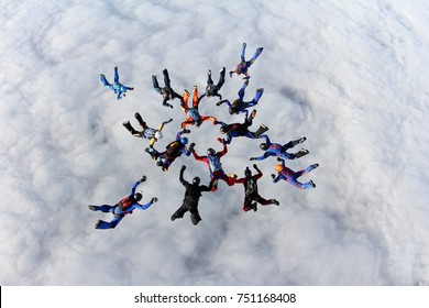 Formation skydiving above white clouds.