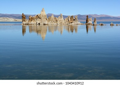 A formation of tufas reflect in the calm water of Mono Lake in northern California on a sunny afternoon.