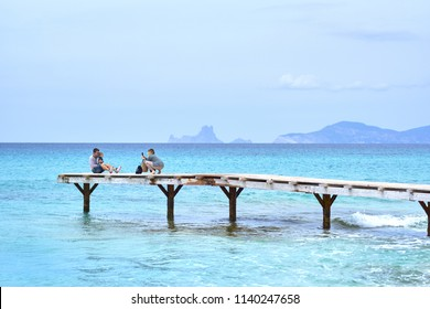 Formentera Island, Spain - May 4, 2018: People person vacationers take a picture, photo in wooden boardwalk, path, picturesque view turquoise water at Ibiza Formentera Island. Balearic Islands. Spain