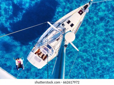 Formentera, Spain - June 10, 2017: Person people relaxing resting on a inflatable boat, yacht and clear smooth lagoon Mediterranean sea, view from mast. Above view, Formentera. Balearic Islands. Spain
