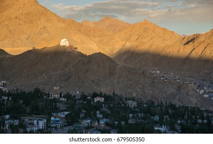 The former royal palace of Leh among the Himalayan mountain in July at sunset. At the background is the line of Himalayan mountain and Leh city,  Leh, Ladakh, India