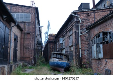 Former shipyard areas - abandoned buildings and boat. The Imperial Shipyard Trail,  Gdansk Shipyard, Poland