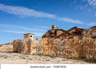 Former stone quarry with abandoned crusher and conveyor machines. Apulia region, Italy.