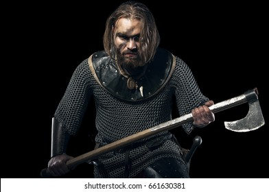 Formidable viking in armor and axe on black background