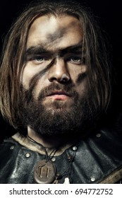 Formidable viking in armor on black background