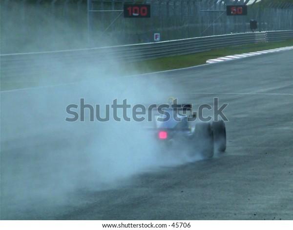 Formula race car splashing through a wet track