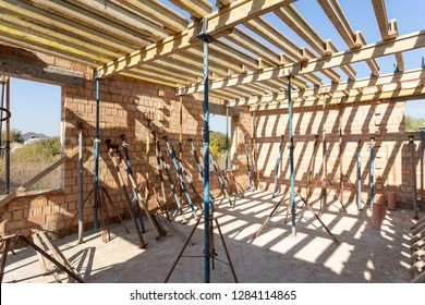 Formwork construction concept. Low angle top view photo of big empty room in incomplete family house with support pillars