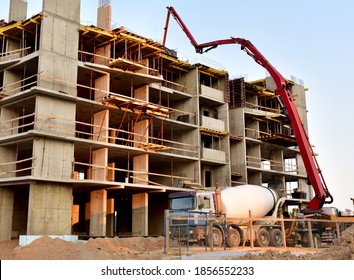 Formworks and pouring concrete through a сoncrete pump truck connected to a ready-mixed truck. Concrete line and boom pumping at construction site. Tower cranes construct residential building