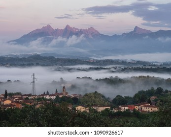 Fornoli village in Lunigiana, north Tuscany, Italy. Misty evening. Apuan Alps mountains behind lit by sunset.