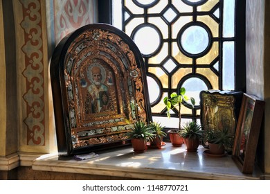 FOROS, CRIMEA, RUSSIA - May 05, 2017 Interior of Church of Christ's Resurrection in Foros. Richly decorated old icon of St. Nicholas with other icons and flowers on window sill.