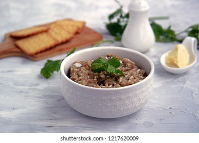 Forshmak, an appetizer of minced herring fillet with apple, onion and egg in a white bowl. Served with unsweetened wheat crackers. Jewish cuisine.