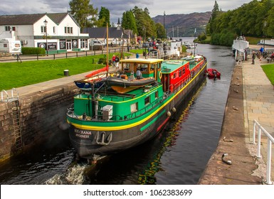 FORT AUGUSTUS, INVERNESS-SHIRE, UK - OCTOBER 4, 2016: Converted barge Ros Crana, on the Caledonian Canal at Fort Augustus transits the last of the locks, into Loch Ness in the Scottish Highlands.