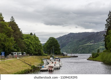 Fort Augustus, Scotland - June 11, 2012: Silver Oich Canal with pleasure boat dock empties in Loch Ness, flanked by green forests on hills at the horizon under heavy gray skies. Boats and RVs.