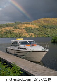 Fort Augustus, UK - September 6, 2019:  A holiday hire cruiser is moored on a pontoon on the Caledonian Canal at Fort Augustus, Scotland, UK, with a rainbow against a dark, foreboding sky.