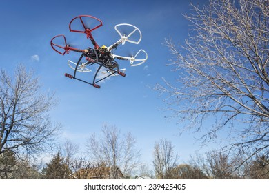 FORT COLLINS, CO, USA, December 20,  2014:  DJI  F550 Flame Wheel  hexacopter drone, assembled from a kit, flying in a backyard among trees.