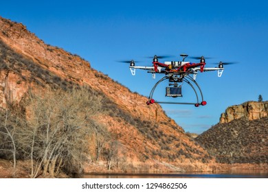 Fort Collins, CO, USA - February 18,  2015:  DJI F550 Flame Wheel  hexacopter drone is  flying with a camera over mountain lake.